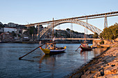Traditional ships on the Douro river with Ponte Dom Luis I bridge in Porto at sunset, Portugal
