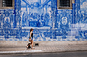 Tourist in Porto in front of blue mural in the street, Portugal