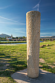 Roman memorial column at Ponte de Lima bridge with church at day, Portugal