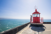 Woman looking out to sea at Nazare lighthouse, Portugal