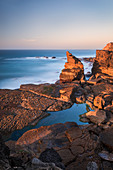 Peniche rocky coast with sea in sunset, Portugal