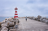 Woman on breakwater and breakwater at the lighthouse of the port of Peniche, Portugal
