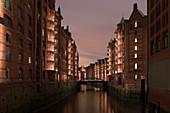 Illuminated warehouse district in Hamburg at night, Germany
