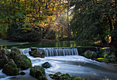 Waterfall at Schwabinger Bach in the English Garden in autumn in the afternoon in Munich, Bavaria