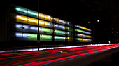 Colorfully lit apartment building with car lights at night, Munich
