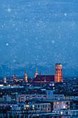 Munich city skyline with illuminated Frauenkirche during snowfall at night