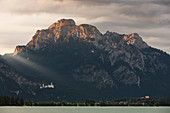 Forggensee with Neuschwanstein Castle and Hohenschwangau in the Ammer Mountains at sunrise, Bavaria