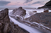 Waves surge around the jagged rocks on Wildersmouth Beach, Ilfracombe, Devon, England, United Kingdom, Europe