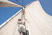 Ein Ägypter klettert auf den Mast eines traditionellen Felucca-Segelboots mit Holzmasten und Baumwollsegeln auf dem Nil, Assuan, Ägypten, Nordafrika, Afrika