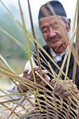 Ein alter nepalesischer Mann webt aus Bambus einen traditionellen Korb, Kathmandu-Tal, Nepal, Asien