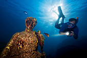 Scuba diver swimming above a submerged ancient Roman statue, underwater Roman ruins, Baia, Campi Flegrei (Phlegraean Fields), Campania, Italy, Europe