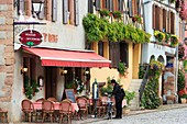 France, Haut Rhin, Route des Vins d'Alsace (Route of the wines of Alsace region), Bergheim, man with a bicycle by the terrace of a cafe on the main square of the village