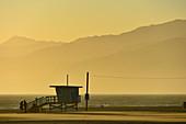 Lifeguard guardhouse on the beach in the golden light of dusk, Santa Monica, California, USA