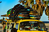 Surfboards and old VW bus with palm trees on Santa Monica Beach, California, USA