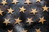 High angle close up of freshly baked star-shaped cookies dusted with icing sugar on black background.