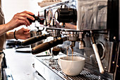 Close up of person making a cappuccino using commercial espresso machine.