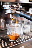 A commercial expresso machine in a coffee shop making an expresso shot.