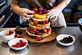 Köchin in einer gewerblichen Küche garniert einen geschichteten Biskuitkuchen mit frischem Obst und Sahne
