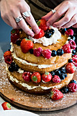A woman cook asembling a layer cake with fresh cream and fresh fruit, strawberries and blueberries.
