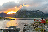 Low clouds swirling round and covering the mountains, a small traditional rorbu house on the shoreline.  Lofoten Islands