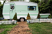 White and green retro caravan parked at the end of a garden path behind low white picket fence.