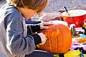 A six year old boy carving pumpkin outdoors at Halloween.