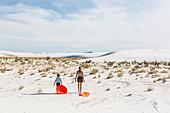children pulling sleds, White Sands Nat'l Monument, NM