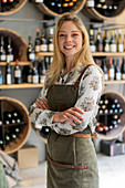 Young woman wearing apron standing in wine shop