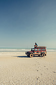 Man sitting on off-road vehicle at 80 Mile Beach in Western Australia, Australia, Indian Ocean, Oceania;