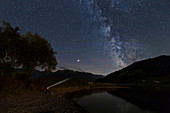Man with headlamp under milky way in the night sky over Sihlsee, Einsiedeln Switzerland