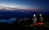 Hikers sit on Jochberg overlooking Kochelsee from above after sunset, Bavaria