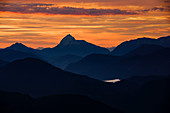 Mountain silhouettes of the Bavarian Prealps on Lake Walchensee in sunrise, from Jochberg