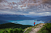 Person on Jochberg with a view of turquoise Walchensee at sunrise, Bavaria