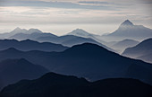 Mountain silhouettes of the Bavarian Prealps on Lake Walchensee with fog, from Jochberg
