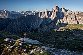 Man in mountain landscape in the Dolomites below the Lavardo hut at the Three Peaks in the sunrise, South Tyrol