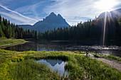 Holzbrücke am See Antorno mit Spiegelung der Drei Zinnen am Tag mit Sonne in den Dolomiten, Südtirol
