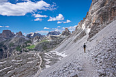Man hiking below the Paternkofel at the Three Peaks in the Dolomites Nature Park, South Tyrol