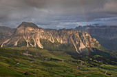 Mountain flank at Seceda with thick clouds, sun and rainbow in the Dolomites near Ortisei, South Tyrol