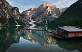 Boathouse with boats on Lake Braies at sunset in the Dolomites, South Tyrol
