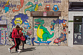 GIRLS PASSING IN FRONT OF A GRAFFITI-COVERED WALL IN A NEIGHBORHOOD IN BROOKLYN, NEW YORK CITY, NEW YORK, UNITED STATES, USA
