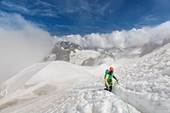MOUNTAINEER CLIMBING UP A SNOW-COVERED SLOPE EMERGING FROM THE CLOUDS IN THE HEART OF THE MASSIF OF THE MONT-BLANC, CHAMONIX-MONT-BLANC, HAUTE-SAVOIE (74), FRANCE