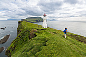 HIKER ON A TRAIL ALONG THE VERDANT CLIFFS OF THE ISLAND OF MYKINES NEAR A LIGHTHOUSE, MYKINES, FAROE ISLANDS, DENMARK