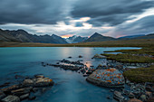 LAST LIGHT OF DAY AND STORMY SKY ABOVE A TURQUOISE BLUE LAKE AT THE FOOT OF THE ALTAI MOUNTAINS, BAYAN-OLGII PROVINCE, MONGOLIA