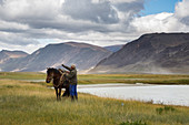 RIDER GETTING HIS HORSE READY NEAR A LAKE SURROUNDED BY MOUNTAINS, TAVAN BOGD MASSIF, ALTAI, BAYAN-OLGII PROVINCE, MONGOLIA