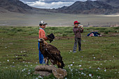 KAZAKH CHILDREN PLAYING AROUND THEIR FAMILY'S GOLDEN EAGLE TRADITIONALLY USED IN HUNTING, TAVAN BOGD MASSIF, ALTAI, BAYAN-OLGII PROVINCE, MONGOLIA