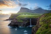 HIKER CONTEMPLATING THE MOUNTAINS, THE CLIFFS AND THE WATERFALL CASCADING INTO THE SEA BY THE VILLAGE OF GASADALUR, VAGAR, FAROE ISLANDS, DENMARK