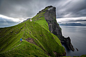 HIKER ON A STEEP PATH NEAR THE KALLUR LIGHTHOUSE IN FRONT OF THE ABRUPT SEA CLIFFS, KALSOY, FAROE ISLANDS, DENMARK