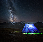LIT-UP MONGOLIAN TENT IN FRONT OF THE NIGHT SKY AND A LUMINOUS MILKY WAY, MOUNT KHUITEN BASE CAMP, ALTAI MOUNTAINS IN THE BACKGROUND, BAYAN-OLGII PROVINCE, MONGOLIA