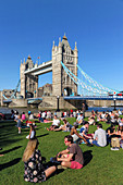 GROUP OF PEOPLE SITTING ON THE LAWN IN FRONT OF TOWER BRIDGE, LONDON, GREAT BRITAIN, EUROPE