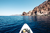 View from the stand-up paddle board at the fascinating volcanic rock in the Scandola Nature Reserve, Galeria, Calvi, Corsica, France